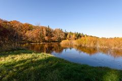 Lake with water reflections in colorful autumn day with colored. Lake with water reflections in colorful autumn day with white clouds in blue sky and colored Royalty Free Stock Image