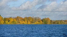 Lake with water reflections in colorful autumn day. With white clouds in blue sky Stock Photo