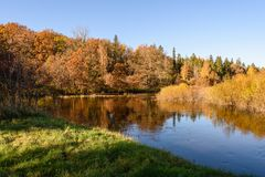 Lake with water reflections in colorful autumn day with colored. Lake with water reflections in colorful autumn day with white clouds in blue sky and colored Stock Image