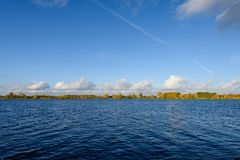 Lake with water reflections in colorful autumn day. With white clouds in blue sky Stock Images