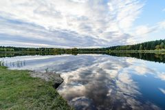 Lake with water reflections in colorful autumn day. With white clouds in blue sky Stock Photos