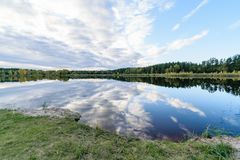Lake with water reflections in colorful autumn day. With white clouds in blue sky Stock Image