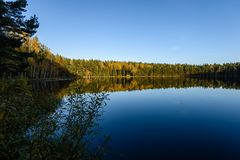 Lake with water reflections in colorful autumn day. With white clouds in blue sky Royalty Free Stock Photography
