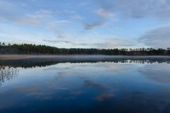 Lake with water reflections in colorful autumn day. With white clouds in blue sky Stock Photography
