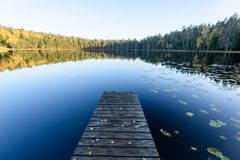 Lake with water reflections in colorful autumn day. With white clouds in blue sky with old wooden boardwalk Royalty Free Stock Photos