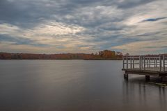 Pier and lake on a cloudy day. Lake water shot in long exposure glassy water with pier in the royalty free stock image