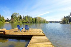 Lake waterfront with pier and two blue chairs. Royalty Free Stock Image
