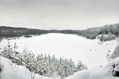 Lake in winter. A frozen lake in the middle of a forest stock photo
