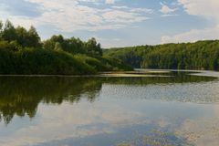 Lake with wooded shore. And sky reflection stock photos