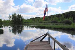 On the lake. Wooden platform with the flag stock photos