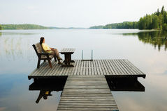 Lake with wooden platform and woman resting. Country landscape with a forest lake. Woman is sitting in the wooden armchair. She is resting on the planked Stock Photography