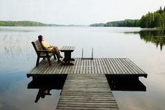 Lake with wooden platform and woman resting. Woman is sitting in the wooden armchair. She is resting on the planked platform near quiet lake Stock Photo