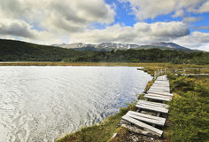 Lake and wooden walkway with moutains on background Royalty Free Stock Photo