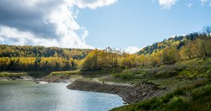 A lake with yellow trees and blue cloudy sky. Dramatic landscape of a lake with blue cloudy sky on yellow autumn tree Royalty Free Stock Images