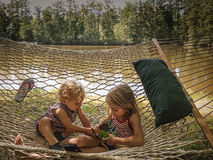 By the Lake. A Young Girl and Boy Lying in a Hammock by the lake Stock Images