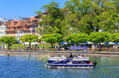 Lake Zug in spring. Zug, Switzerland - 6 May, 2016: people in a boat on Lake Zug with the city of Zug in the background. Lake Zug (German: Zugersee) is a lake in Stock Images