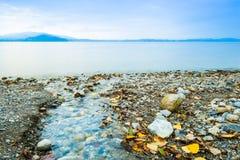Lake Zug. Switzerland. Autumn landscape on the shore of the lake. Long exposure. Yellow foliage and gems on the coast. Lake Zug. Switzerland Royalty Free Stock Images