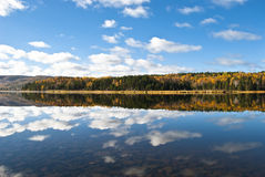 Lakebed Clouds. Cape Breton Autumn Colors and Puffy Clouds Reflected in Glassy Lake with Lake Bed Stones showing through Clear Water in Foreground Royalty Free Stock Images