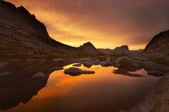 lakeberg near solnedgång Solljus reflekterat på bergblast Guld- ljus från himmel reflekterade i en bergsjö Ergaki royaltyfri fotografi