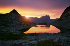 lakeberg near solnedgång Solljus reflekterat på bergblast Guld- ljus från himmel reflekterade i en bergsjö Ergaki arkivfoto