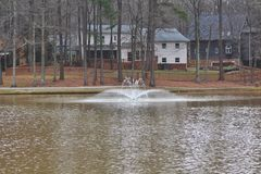 Lakehome surrounded by lake with waterfall. Cary.NC/US February 20,2016 Homes surrounded by a beautiful lake with a waterfall and tall trees royalty free stock images