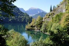 Laken omges av berg och skogar Royaltyfri Bild