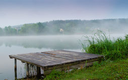 Lakes and the early morning fog. Mystic fog is running on the lake in the cold summer morning. Bridge Lake Stock Photo