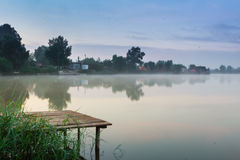 Lakes and the early morning fog. Mystic fog is running on the lake in the cold summer morning. Bridge Lake Stock Photos