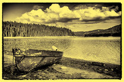 By the lakeshore. An old boat anchored by the shore of a artificial lake in the Apuseni Natural Park Stock Photography