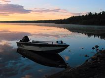 Lakeshore Dawn. A fishing boat stands ashore prior to sunrise stock photo