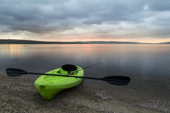 Lakeshore Sunset. Kayak on lake shore with fishing rod royalty free stock image