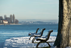 Lakeside benches with snow Royalty Free Stock Photos