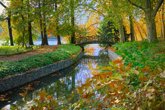 Lakeside Bridge in Park. Autumn view of a bridge over a stream leading into the lake at Golden Head Park in Lyon, France Stock Photo