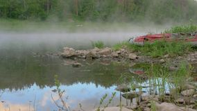 Lakeside with brown stones and red boat by calm water. Lakeside with brown stones and grey red inflatable rubber boat by calm water with morning fog against stock video