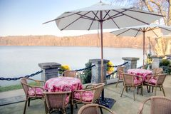 Lakeside cafe tables. A terrace with some tables, umbrellas and chairs, near a lake, nobody in the photo Stock Images