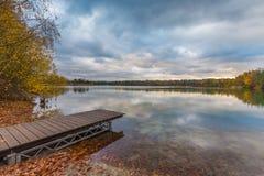 Lakeside con il molo, le foglie cadute e il treeline nei colori luminosi di autunno immagini stock