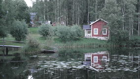 Lakeside cottage in Finland. Reflected in pond Stock Photos