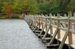Lakeside Foot Bridge in Autumn. A weathered wooden foot bridge spans across a small lake Stock Photography