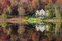 Lakeside Getaway House. A beautiful lakeside home nestled among colorful trees displaying autumn foliage royalty free stock images