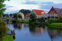 Lakeside holiday homes morning idyll. Dutch holiday homes with porches and jetties situated at a lake. Peaceful morning idyll with ducks in summer Stock Photo