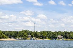 Lakeside homes and boat docks with trees and a transmitter tower in the background under a blue sky with fluffy clouds stock image