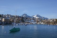 Lakeside homes and sailboat seen from a cruise boat at Lake Thun, Switzerland, Europe. Winter 2017 Royalty Free Stock Image