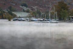Yachts beyond mist on lake Stock Photo