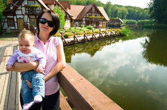 Lakeside house family. Family of mother and baby daughter in front of a lakeside house Royalty Free Stock Image