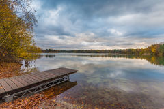 Lakeside with jetty, fallen leaves and treeline in bright autumn colors. Early morning scenic view with cloudy sky and its reflection on the water surface Stock Images