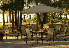 Lakeside Patio. With a table and umbrella and chairs amid the trees. landscaped Royalty Free Stock Photo