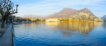 The lakeside promenade, Lugano. LUGANO, SWITZERLAND - DECEMBER 29, 2015: Panoramic view of the lakeside promenade, with locals and visitors, in Lugano, Ticino royalty free stock image