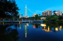 Lakeside scenery of Taipei 101 Tower among skyscrapers in Xinyi District Downtown at dusk with view of reflections on the pond. In an urban park Stock Photography