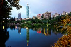 Lakeside scenery of Taipei 101 Tower among skyscrapers in Xinyi District Downtown at dusk with view of reflections on the pond. In an urban park Stock Image