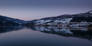 Lakeside village. A village on the shores of a lake in winter. The reflection of the mountains and the lights and the evening light create an atmosphere and a Royalty Free Stock Images